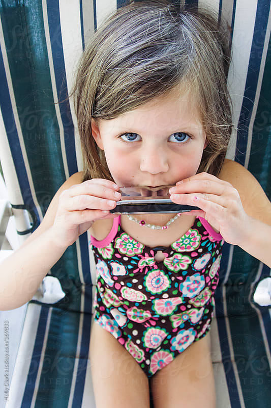 A cute little girl plays the harmonica on a summer day. by Holly Clark for Stocksy United