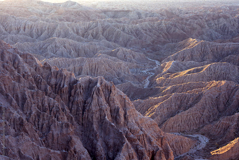 Anza borrego desert southern California at sunrise meandering stream bed eroded ridges badlands by Ron Mellott for Stocksy United