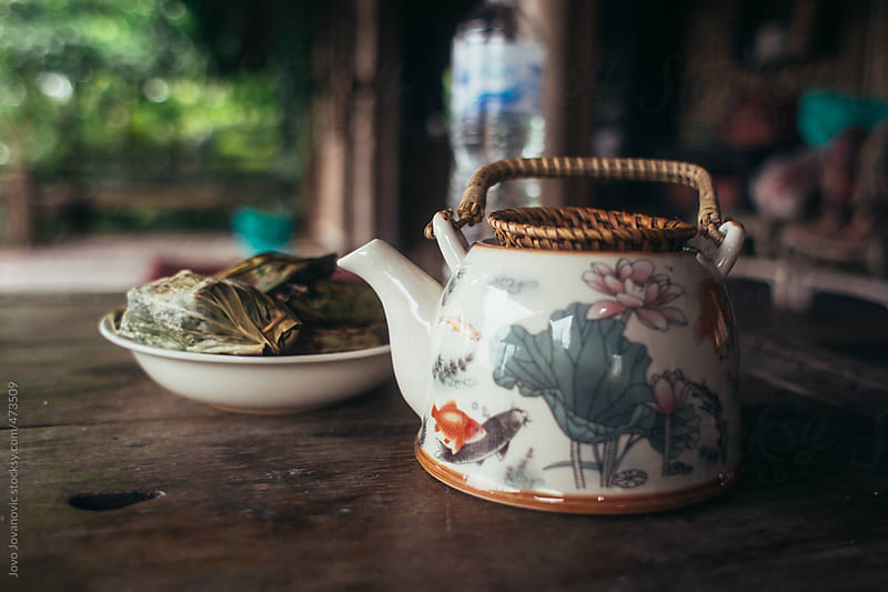 Chinese tea pot and fresh herbs on wooden table by Jovo Jovanovic for Stocksy United