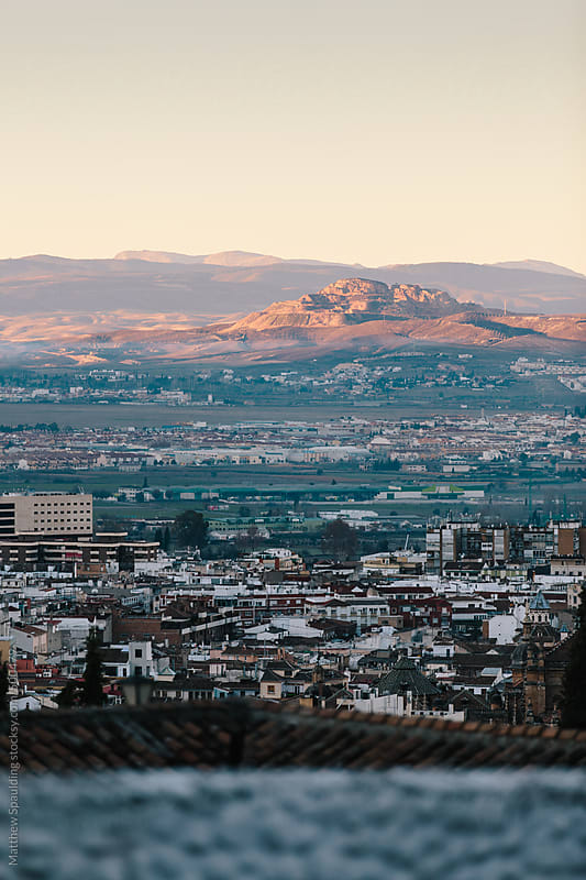 View of sunrise over city and distant mountains in Grenada Spain by Matthew Spaulding for Stocksy United