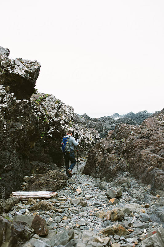 Man hiking rocky coastline - digital file by Andrew Cebulka for Stocksy United