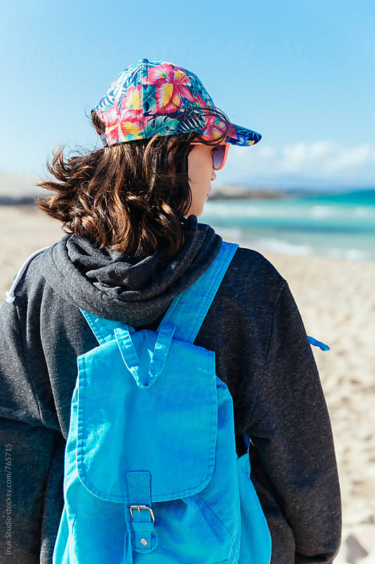 Young woman back view with blue backpack and sweatshirt looking at the sea in a beach by Inuk Studio for Stocksy United