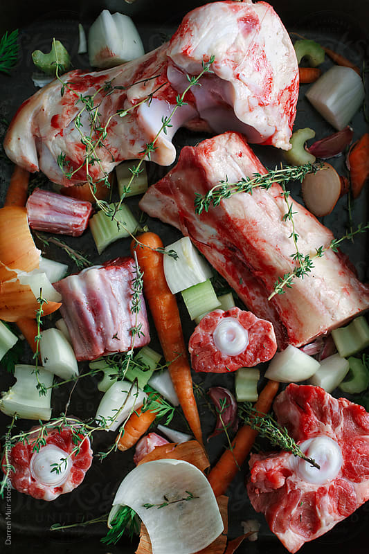 Beef and ox bones in an oven tray with vegetables and thyme. by Darren Muir for Stocksy United