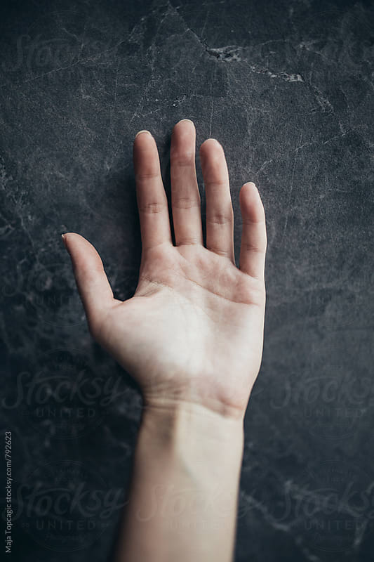 Female hand against a dark background by Maja Topcagic for Stocksy United