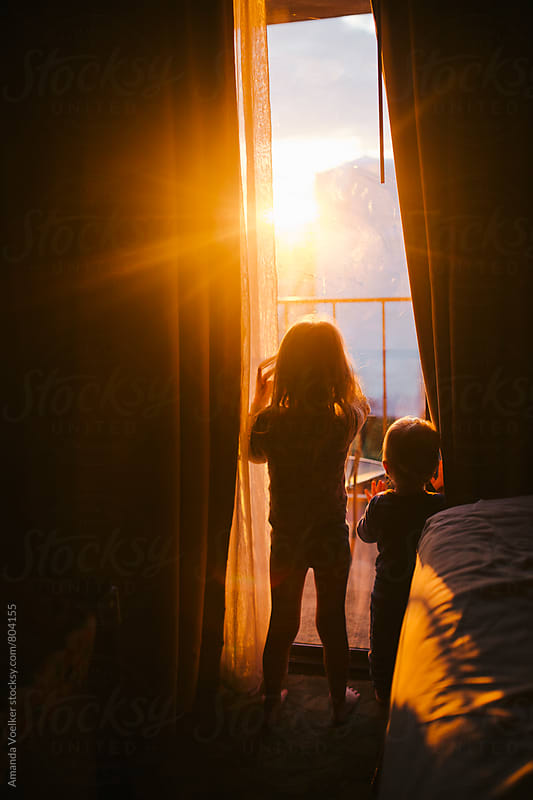 Little girl and toddler brother stand by window and watch the sunrise by Amanda Voelker for Stocksy United