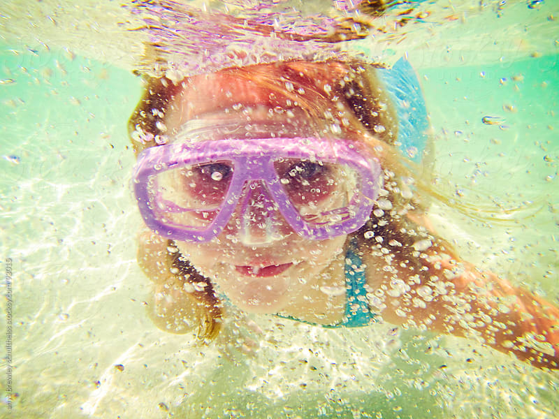 Portrait of young girl swimming underwater with pink goggles by anya brewley schultheiss for Stocksy United