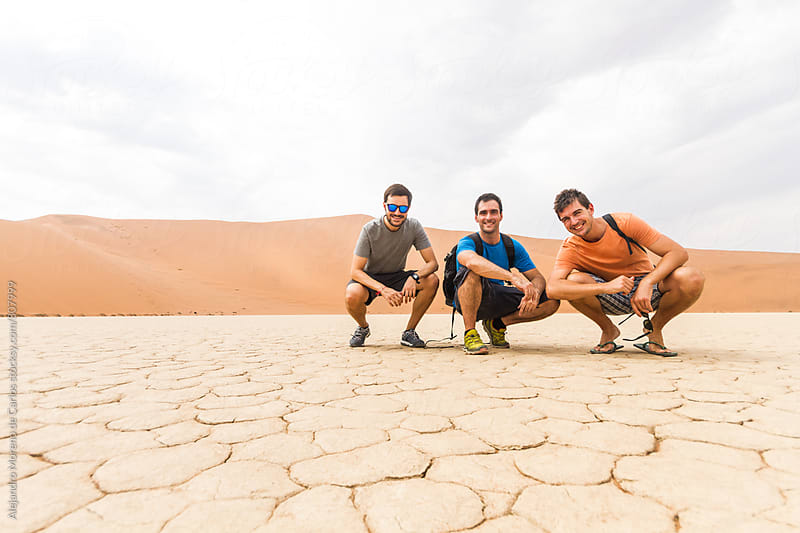 Three young friends crouched down for a picture in the desert in the middle of nowhere by Alejandro Moreno de Carlos for Stocksy United
