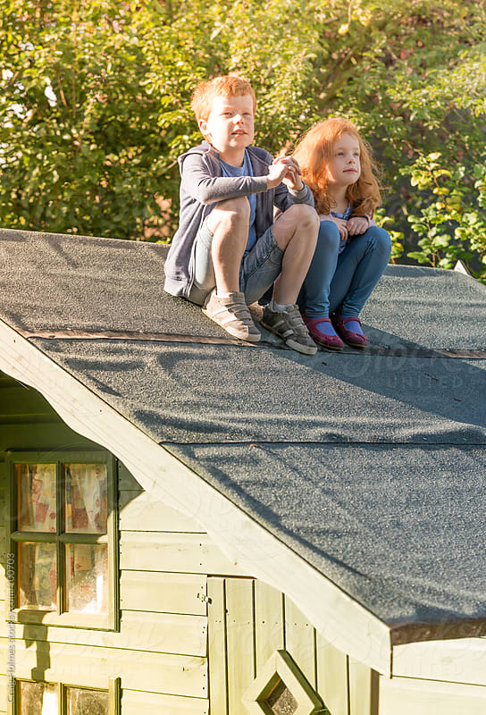Children sitting on top of a shed by Craig Holmes for Stocksy United