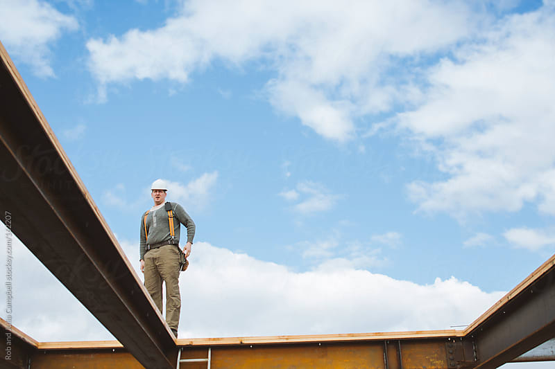 Carpenter man surveys construction site from steel beams by Rob and Julia Campbell for Stocksy United