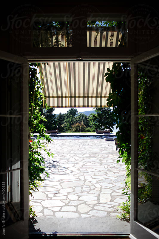 Doorway to pool area with awning  by Jennifer Brister for Stocksy United