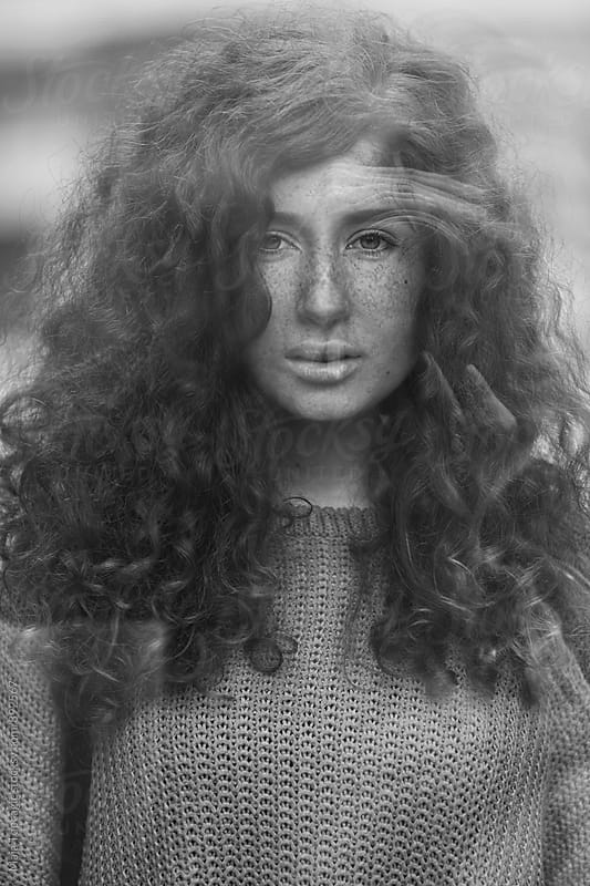 Portrait of a redhead through window by Maja Topcagic for Stocksy United