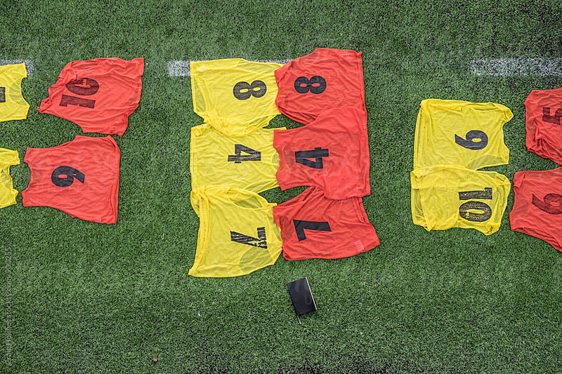 Sports vests laying on grass ready for a match by Craig Holmes for Stocksy United