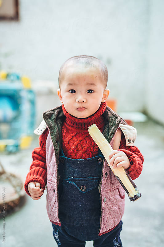 Chinese boy eating sugarcane by Xunbin Pan for Stocksy United