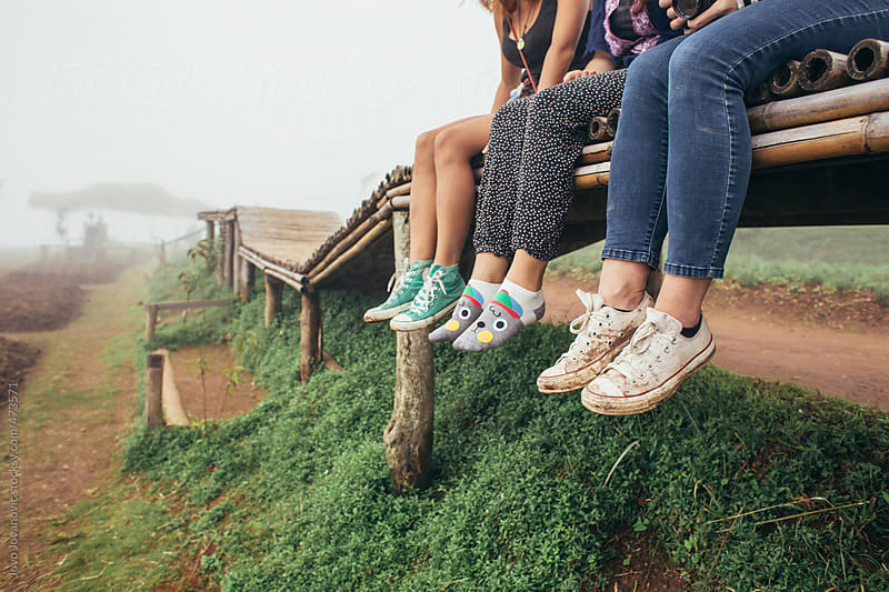Three girls wearing cute sneakers and socks sitting on a wooden bridge in the country side by Jovo Jovanovic for Stocksy United