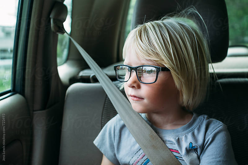 girl looking out car window by Jess Lewis for Stocksy United