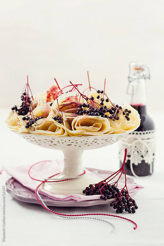 Crepes with elderberry syrup rolled up and arranged on a cake stand by Elisabeth Coelfen for Stocksy United