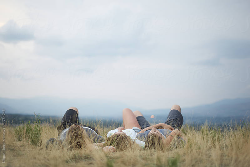 Back view of three teenagers laying on the grass outdoors by Miquel Llonch for Stocksy United