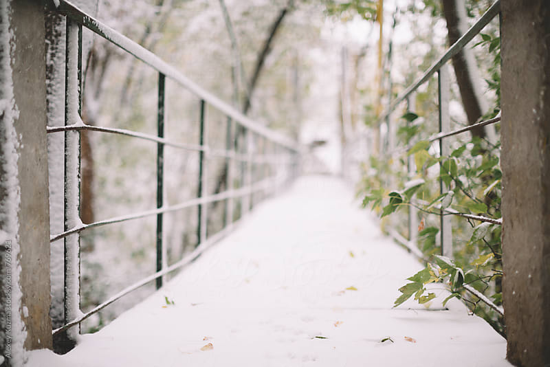 old wooden pedestrian bridge covered with snow, selective focus by Alexey Kuzma for Stocksy United