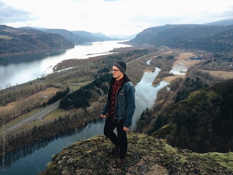 Young male standing on cliff high above river gorge by Jesse Morrow for Stocksy United