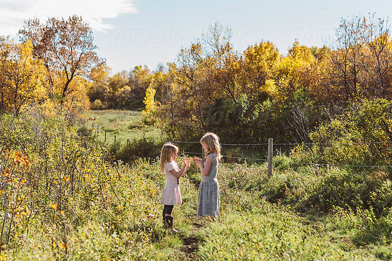 Young girls playing in autumn field by Carey Shaw for Stocksy United