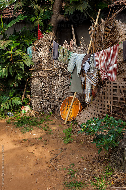 Drying clothes outside the house of the poor by Yury Goryanoy for Stocksy United