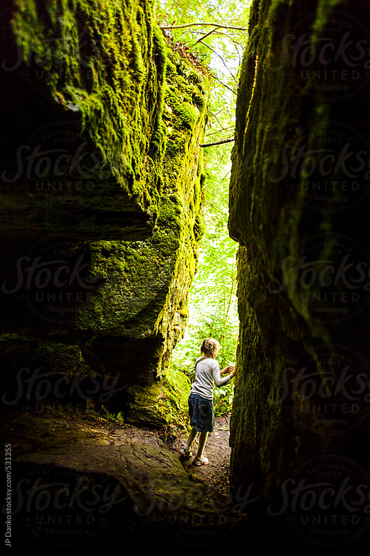 Girl Exploring Cave In Rocky Mossy Mountainside by JP Danko for Stocksy United