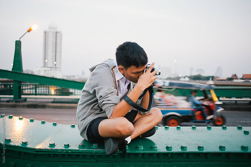 Thai teenage photographer making a picture on the bridge over the river by Nabi Tang for Stocksy United