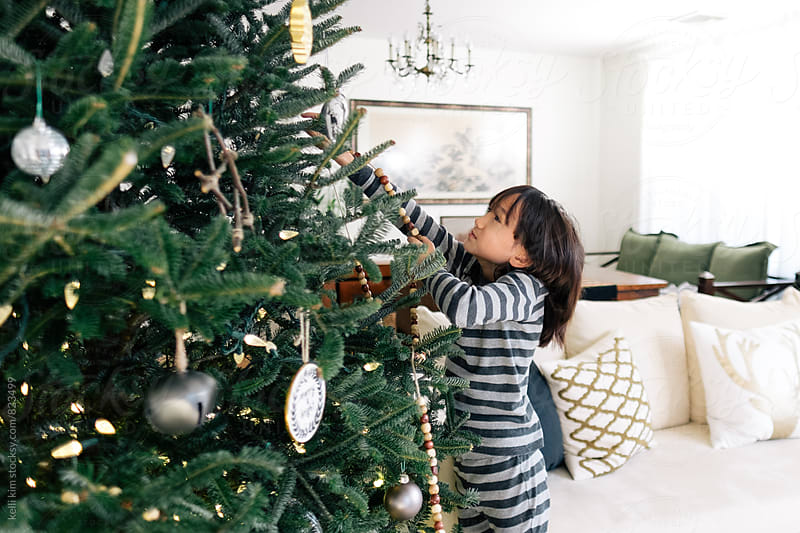 Young mixed race boy decorates Christmas tree by Kelli Seeger Kim for Stocksy United