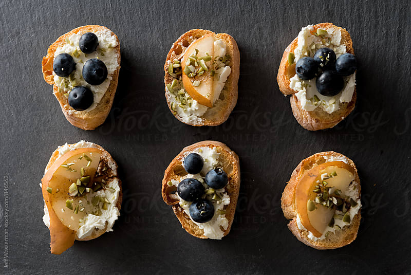 Crostini with Goats Cheese, Pear and Blueberry on Slate by Jeff Wasserman for Stocksy United