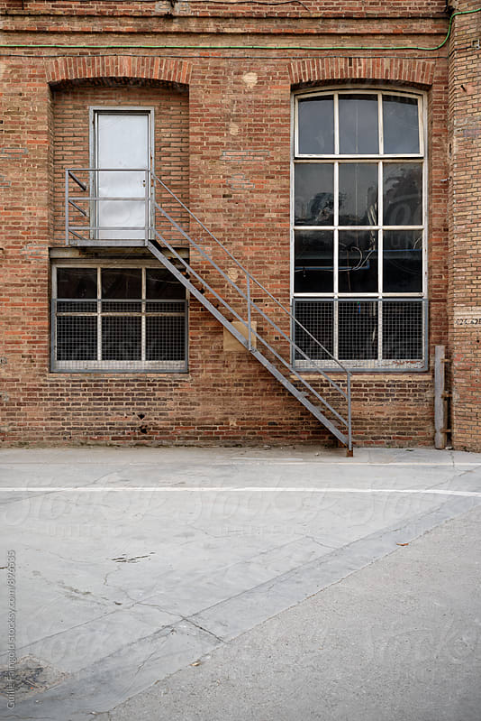 Frontal view of factory facade, old brick wall with window and door by Guille Faingold for Stocksy United