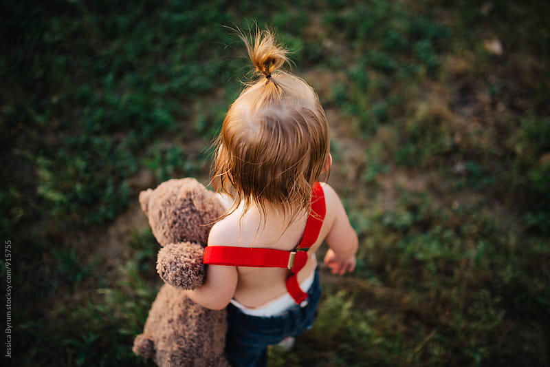 Small toddler child walking around with a teddy bear in red suspenders. by Jessica Byrum for Stocksy United