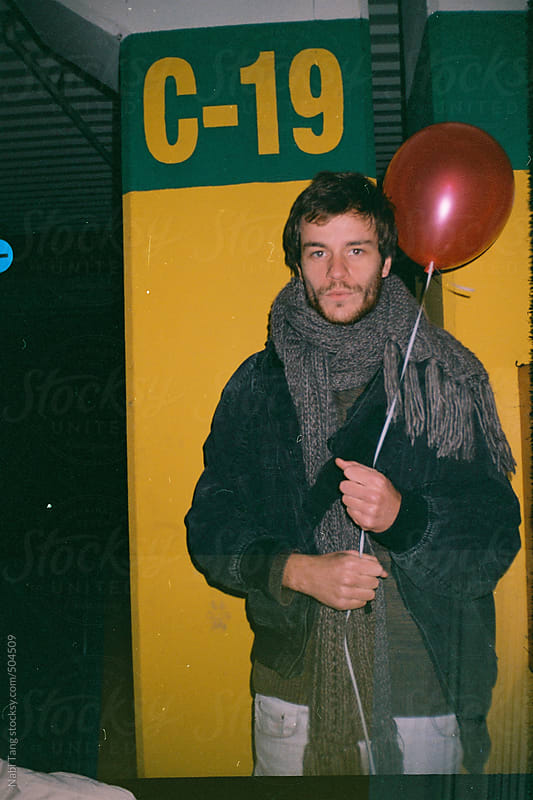 Handsome hipster man holding a red balloon at the underground parking lot by Nabi Tang for Stocksy United