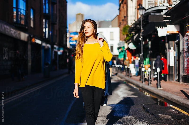 Young Blonde Woman Walking in the Middle of the Street. Dublin City  by HEX. for Stocksy United