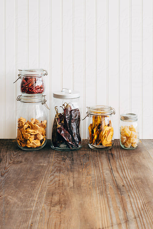 Dried mango, apple, peppers, and ginger in glass jars. by Lucas Saugen for Stocksy United