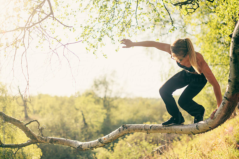 Woman Balancing on a Tree Branch by Willie Dalton for Stocksy United