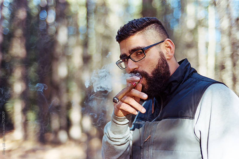 A bearded man exhales cigar smoke by Riley J.B. for Stocksy United