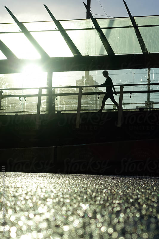 Woman silhouetted on a bridge on Spencer St, Melbourne by Gary Radler Photography for Stocksy United