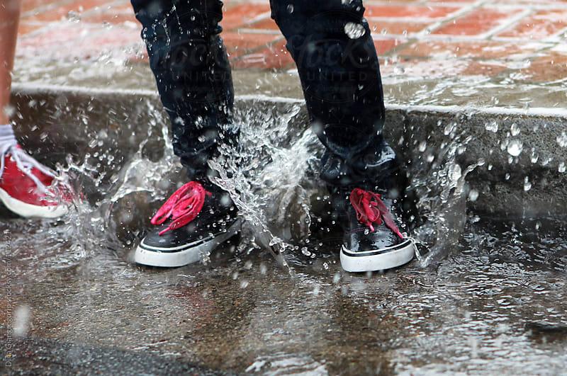 Children splashing in rain water by sidewalk by Dina Giangregorio for Stocksy United
