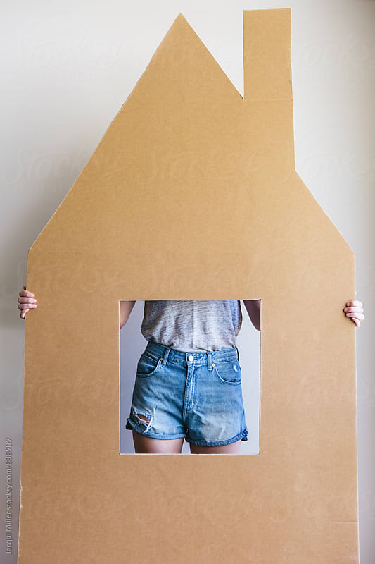 Unrecognisable female holding a large cardboard cut out of a house by Jacqui Miller for Stocksy United