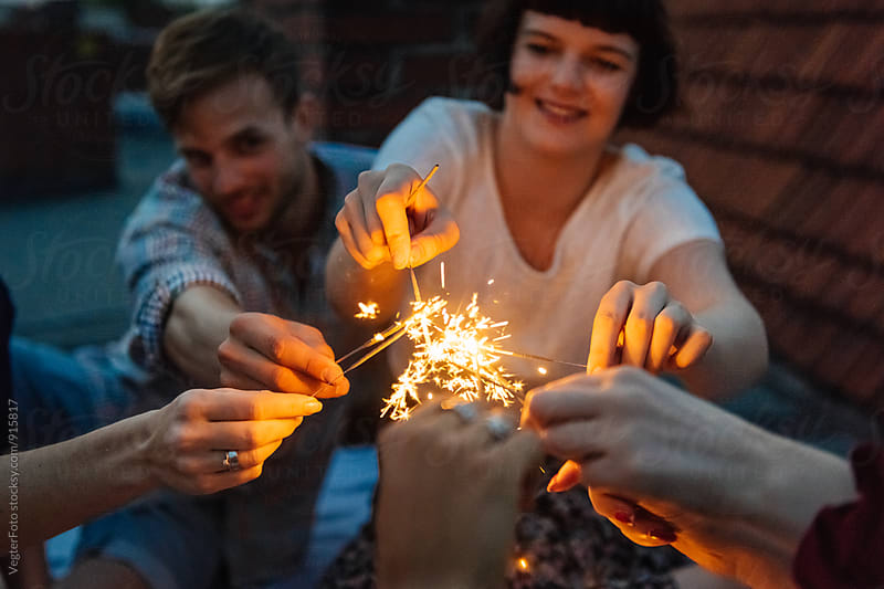 Young adults are lighting sparklers. by VegterFoto for Stocksy United