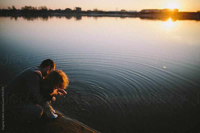 Father and daughter touching water surface of the river  by Evgenij Yulkin for Stocksy United