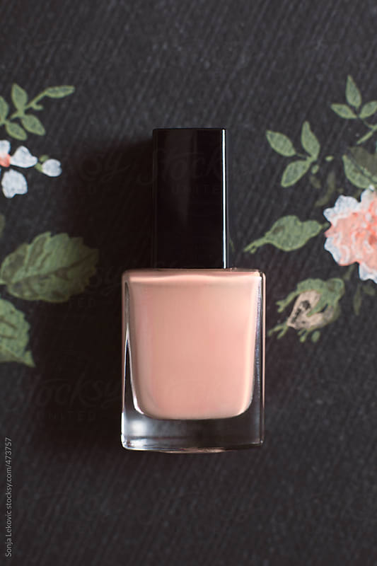 nude color nail polish on dark decorative background by Sonja Lekovic for Stocksy United