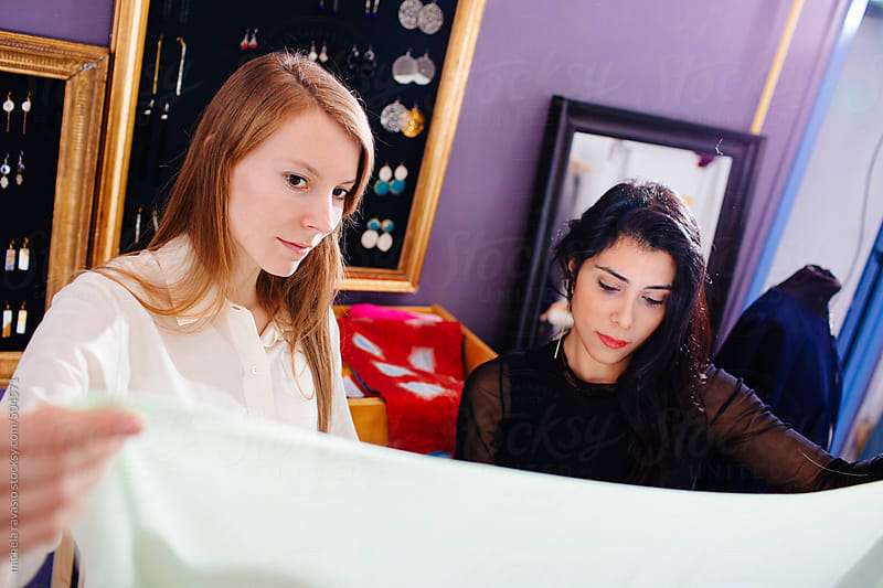 Young fashion stylist  women checking the quality of the cloth by michela ravasio for Stocksy United