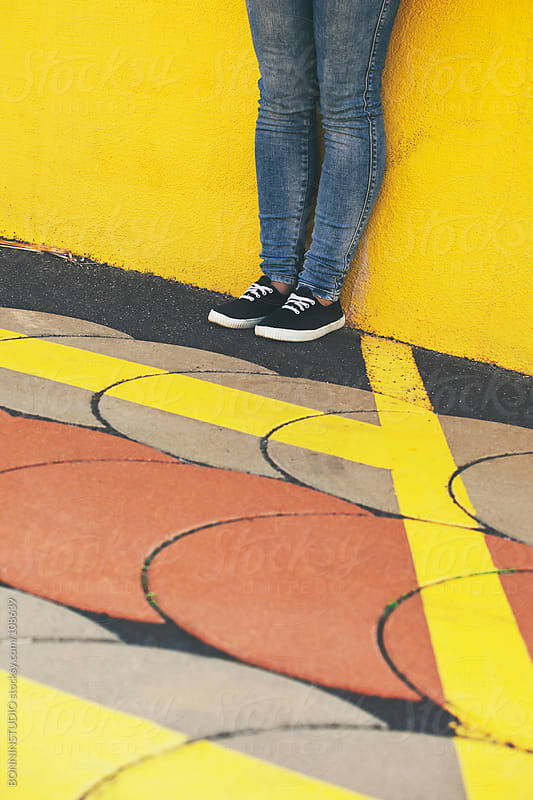 Feet of young girl standing on yellow wall.  by BONNINSTUDIO for Stocksy United