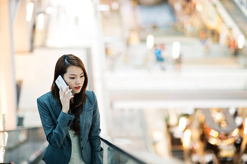 Businesswoman speaking on the phone by Alita Ong for Stocksy United