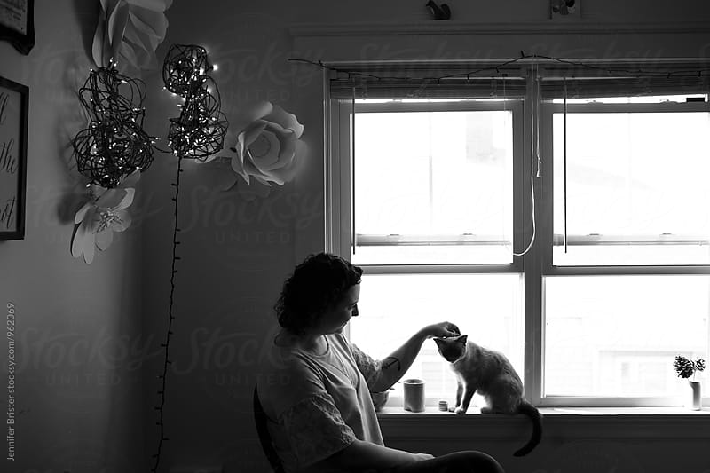 Shadowy image of woman with cat by Jennifer Brister for Stocksy United
