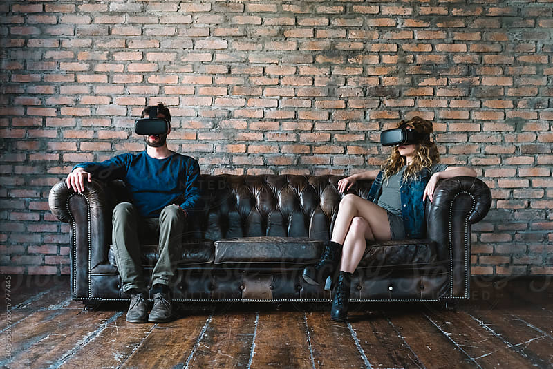 Couple at home using VR Reality viewer by GIC for Stocksy United