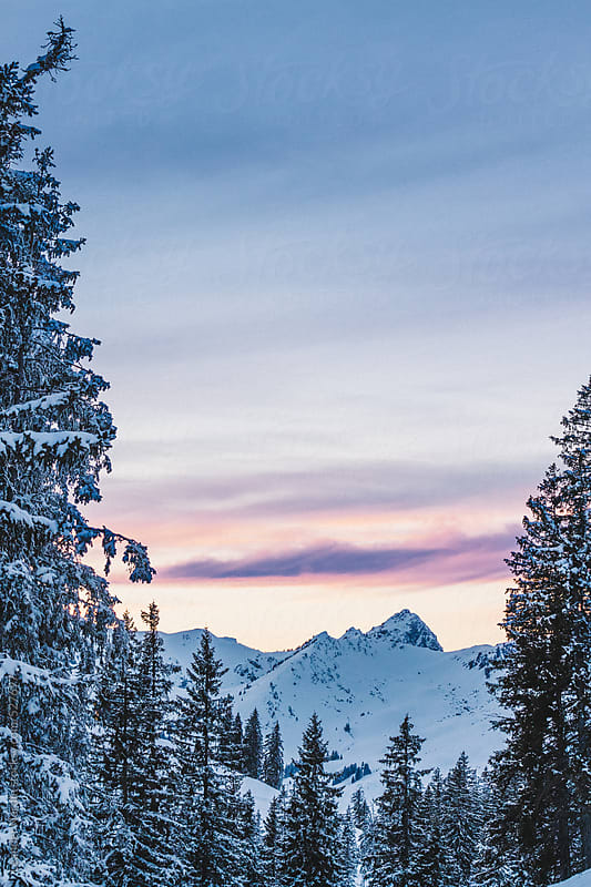 sunrise over snowcovered mountain landscape by Leander Nardin for Stocksy United
