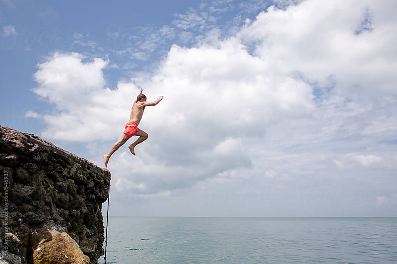 Summer fun - man jumping off cliff into the ocean by Jovo Jovanovic for Stocksy United