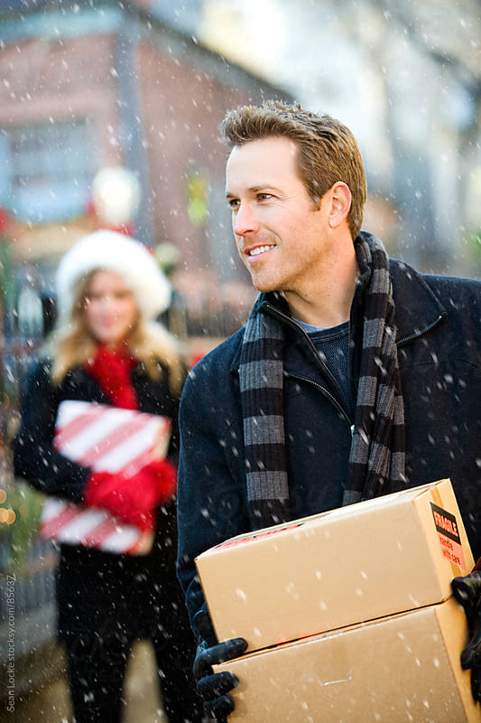 Christmas: Walking with Christmas Packages by Sean Locke for Stocksy United